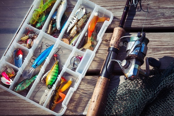 Fishing Lures in tackle boxes with spinning rod and net - Stock Photo - Images