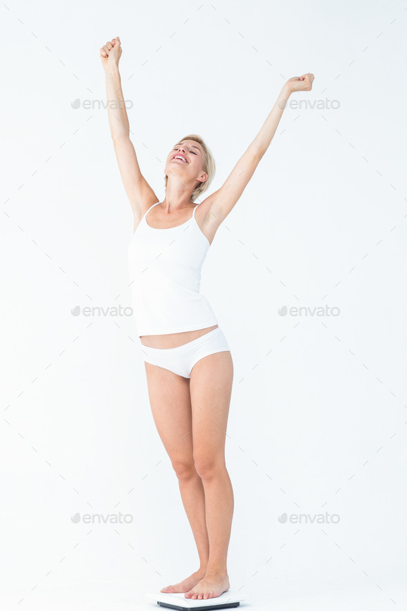 Happy woman standing on a scales spreading her arms on white background - Stock Photo - Images
