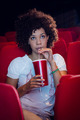 Young woman watching a film and drinking a soda at the cinema - PhotoDune Item for Sale