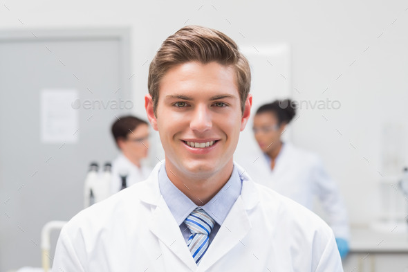 Happy scientist smiling at camera in the laboratory - Stock Photo - Images