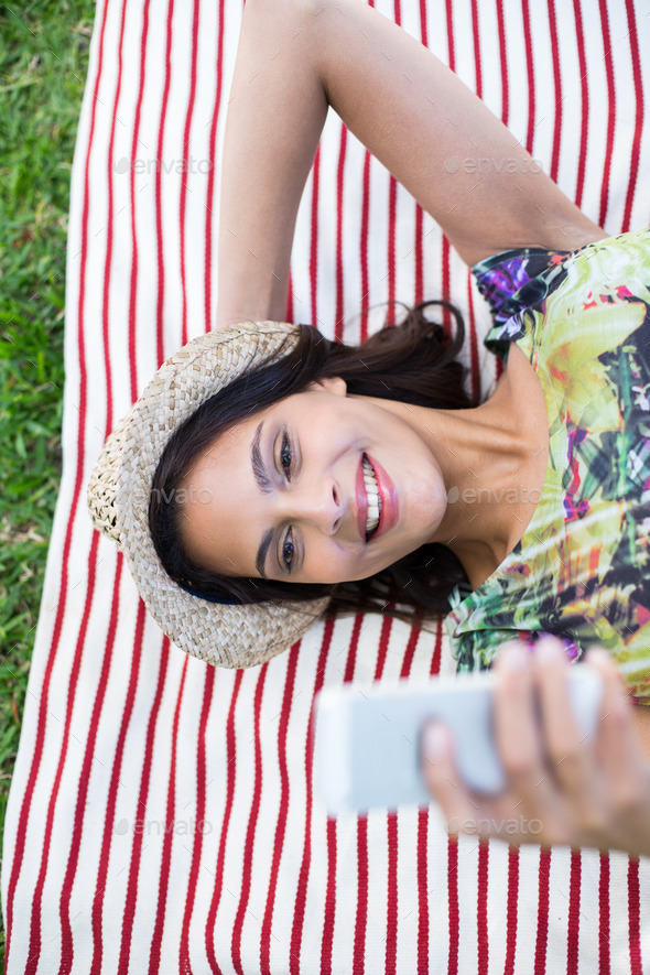Smiling beautiful brunette lying on the blanket and using her phone - Stock Photo - Images