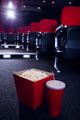 Empty rows of red seats with pop corn and drink on the floor at the cinema - PhotoDune Item for Sale