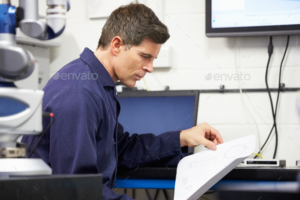 Engineer Looking At Plans With CMM Arm In Foreground - Stock Photo - Images