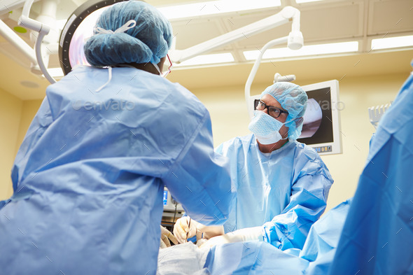 Surgical Team Working In Operating Theatre - Stock Photo - Images
