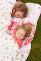 Two Girls Lying Under Blanket On Camping Holiday