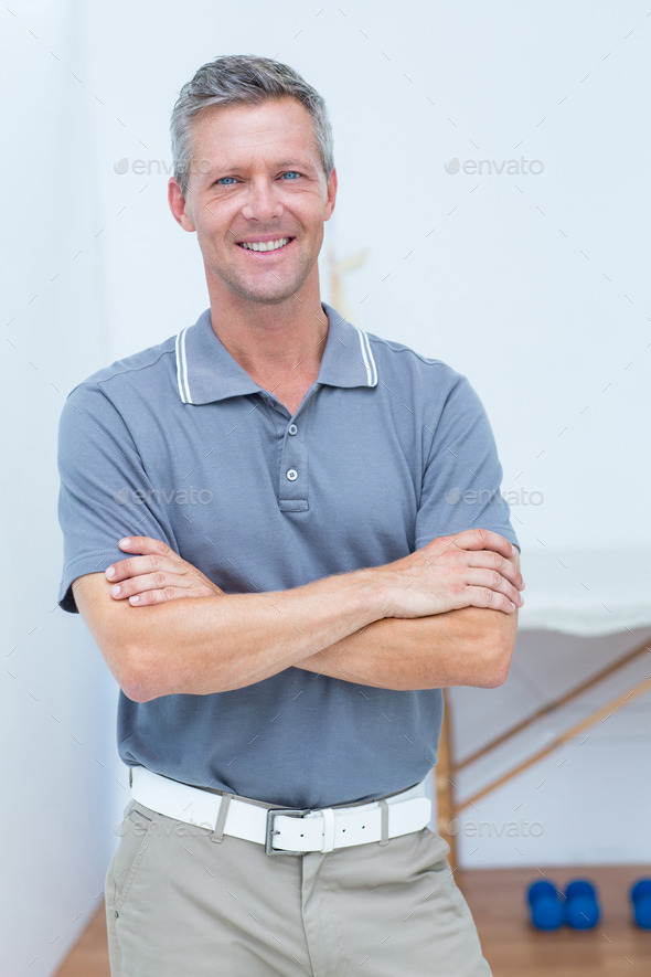 Smiling doctor standing arms crossed in medical office - Stock Photo - Images