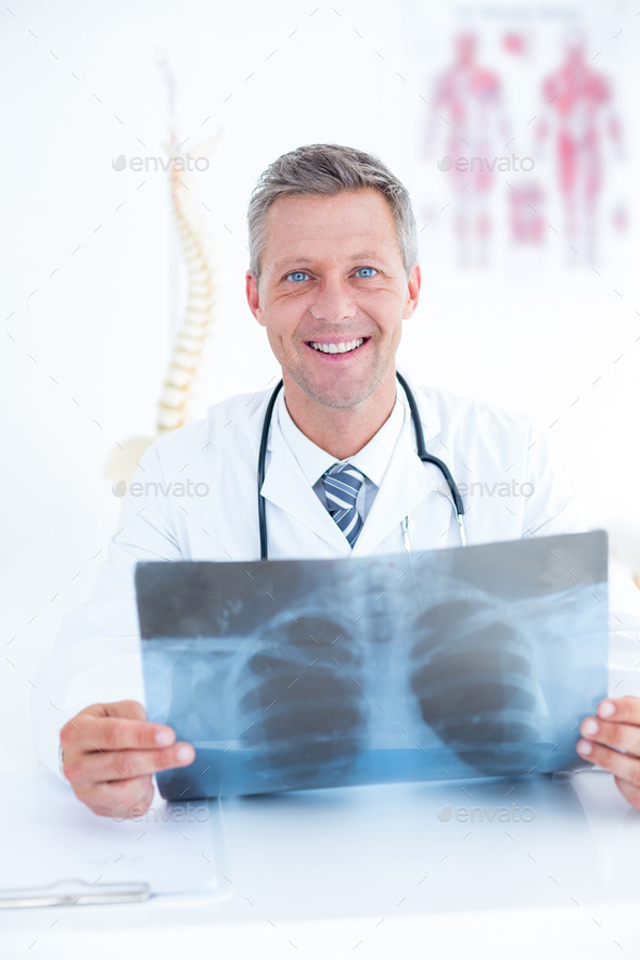 Smiling doctor holding xray in medical office - Stock Photo - Images