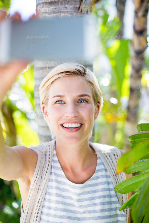 Pretty blonde woman taking selfie in the park - Stock Photo - Images