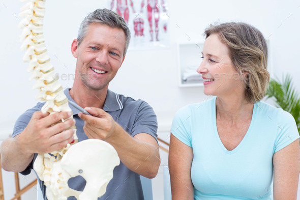 Physiotherapist showing spine model to his patient in medical office - Stock Photo - Images