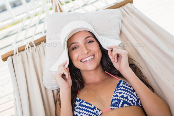 Pretty brunette relaxing on a hammock in patio - Stock Photo - Images