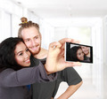 multicultural couple taking self camera together