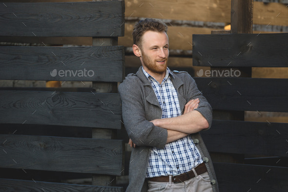 Portrait of young fashionable man against wooden fence - Stock Photo - Images