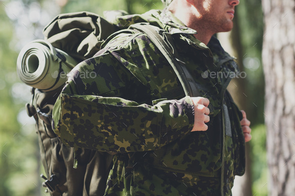 close up of young soldier with backpack in forest - Stock Photo - Images