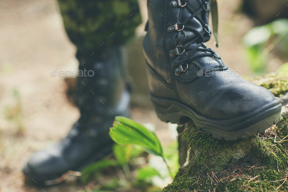 close up of soldier feet with army boots in forest - Stock Photo - Images
