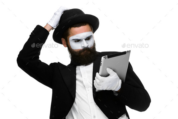 Man with a face mime working on laptop - Stock Photo - Images