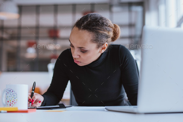 Young woman working at her desk - Stock Photo - Images