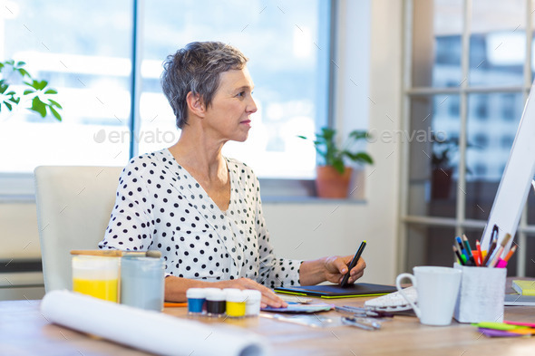 Casual businesswoman drawing with digitizer in the office - Stock Photo - Images