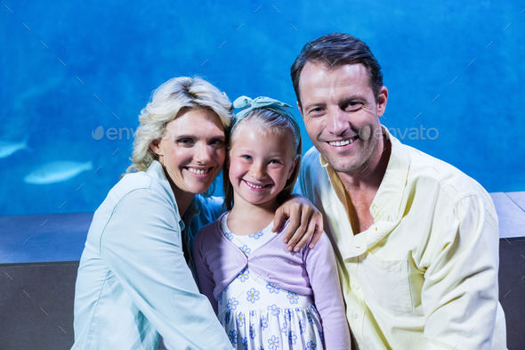 Happy family looking at camera beside the fish tank at the aquarium - Stock Photo - Images