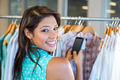 Beautiful brunette scanning bar code with her mobile phone in clothes store