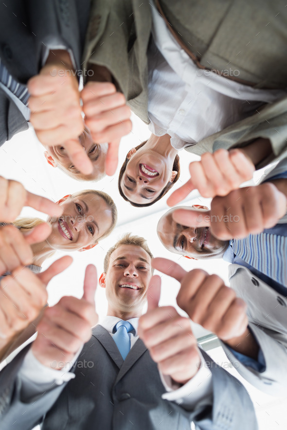 Business colleagues standing in circle and looking at camera in the office - Stock Photo - Images