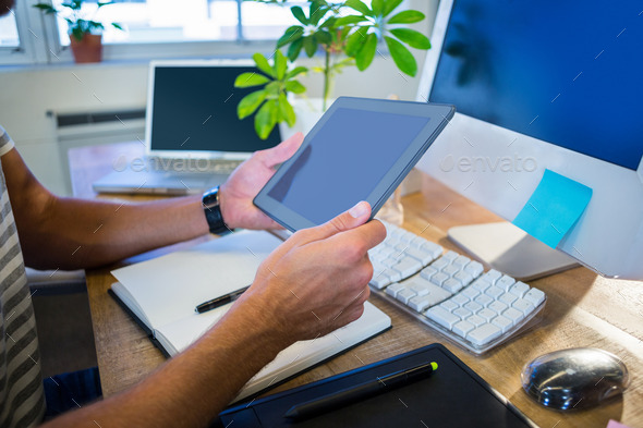 Casual businessman working on tablet at his desk - Stock Photo - Images