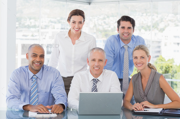Business team during meeting smiling at camera in the office - Stock Photo - Images