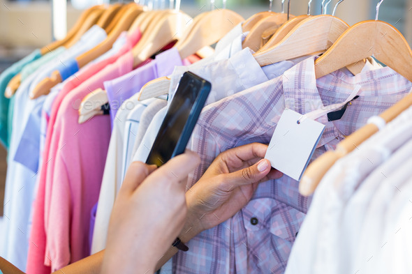 Woman scanning bar code with her mobile phone in clothes store - Stock Photo - Images
