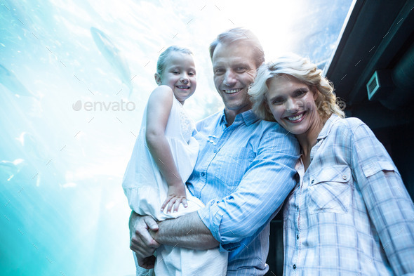 Happy family looking at camera behind a fish tank at the aquarium - Stock Photo - Images