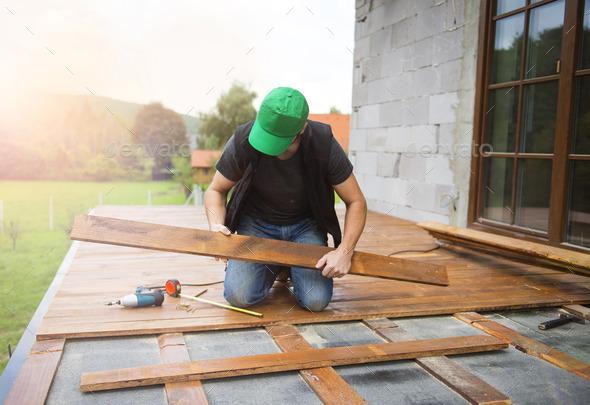 Handyman installing wooden flooring - Stock Photo - Images