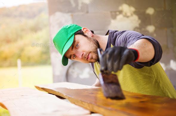 Handyman varnishing wooden planks outside - Stock Photo - Images