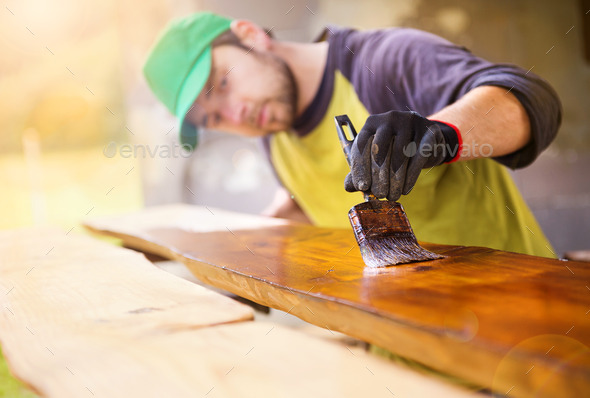 Handyman varnishing wooden planks outside - Stock Photo - Images