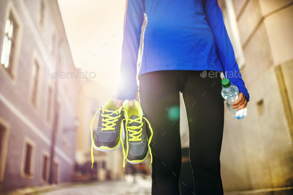 Female runner carrying her shoes - Stock Photo - Images