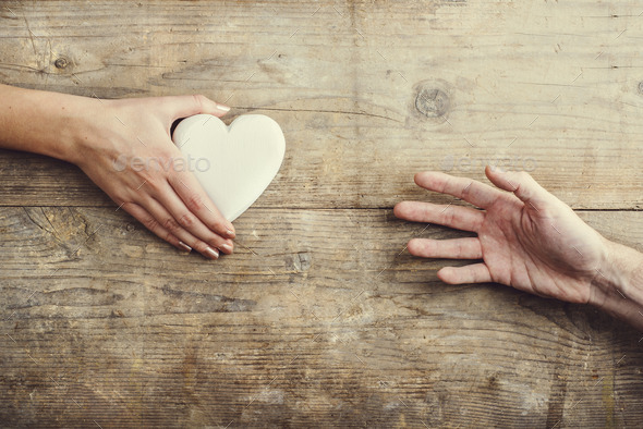 Man reaching for a heart to woman. - Stock Photo - Images