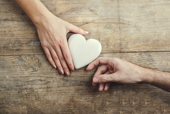 Man offering a heart to a woman. - Stock Photo - Images