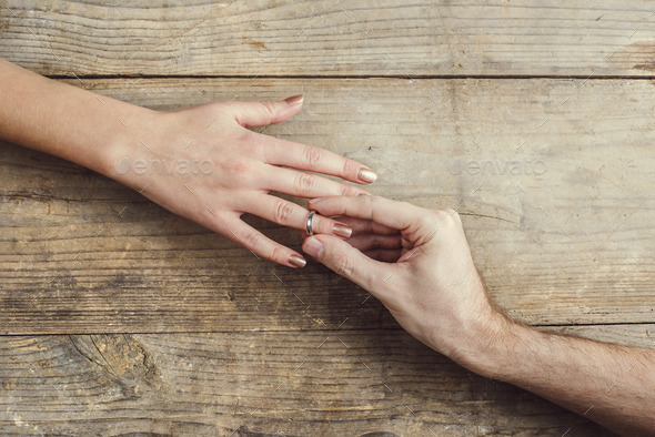 Man putting on an engagement to his woman. - Stock Photo - Images