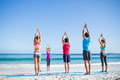 Friends doing yoga together with their teacher at the beach - PhotoDune Item for Sale