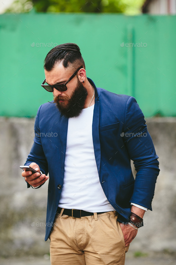 Bearded businessman looking at phone - Stock Photo - Images