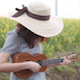 Girl Playing Ukulele Near The Flower Garden - VideoHive Item for Sale