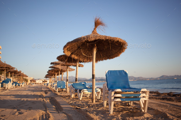 Empty beaxh with straw umbrellas on sunrise - Stock Photo - Images
