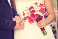 Hands of a bride and groom. Bride holding red lily bouquet