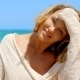 Blond Woman With Hand In Hair Sitting On Beach - VideoHive Item for Sale