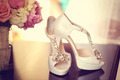 Elegant bride's shoes with a peonies bouquet