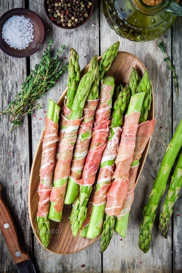 Fresh organic asparagus wrapped in prosciutto on a cutting board - Stock Photo - Images