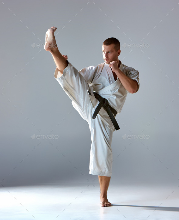 Man in white kimono training karate - Stock Photo - Images