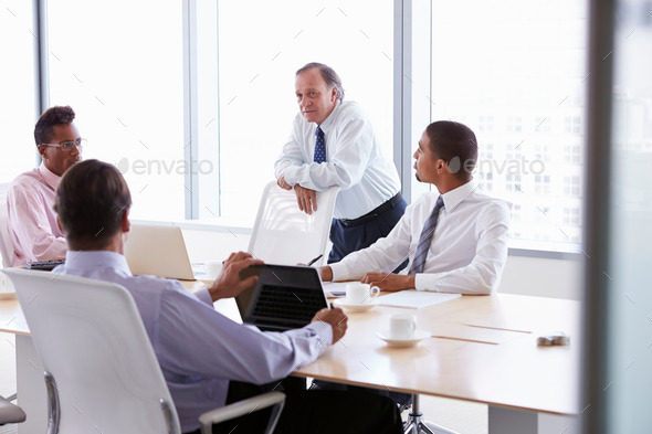 Four Businessmen Having Meeting Around Boardroom Table - Stock Photo - Images