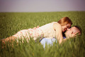Beautiful cheerful couple lying on green grass