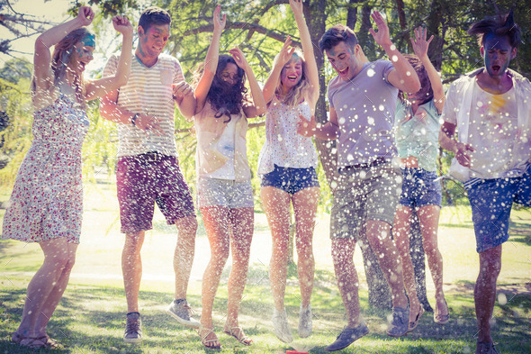 Happy friends jumping in the water shoot on a sunny day - Stock Photo - Images