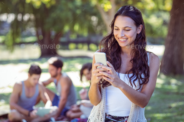 Pretty hipster using her smartphone on a sunny day - Stock Photo - Images