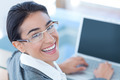 Smiling businesswoman using laptop in an office - PhotoDune Item for Sale