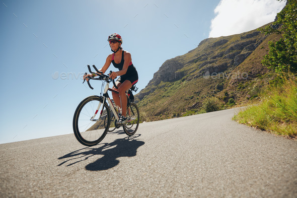 Woman competing in the cycling leg of a triathlon - Stock Photo - Images